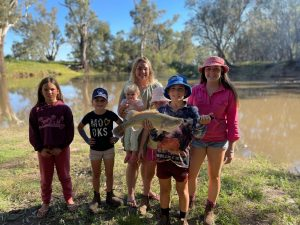 Rubie Haworth, Zahlee Blewitt, Lynette Haworth, Dakotah Haworth, Jaren Blewitt and Arabella Blewitt were happy with their 58 centimetre Murray Cod, caught on the Lachlan River. The fish was released back into the River. Image Credits: Melissa Blewitt.